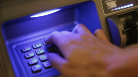 stock-footage-placing-card-into-atm-and-putting-in-pin